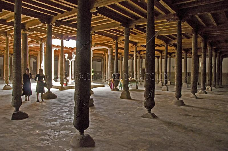 Two young girls stand next to the wooden columns in the Djuma Mosque.