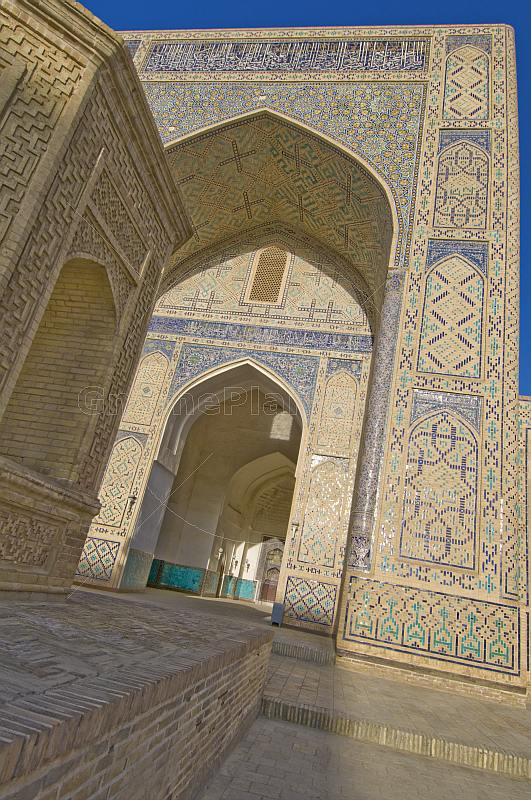 Blue ceramic tilework reflects the sunlight on the arch of the Kalyan Mosque.