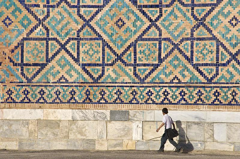 Small boy walks in front of the tiled mosiacs on the Sher-Dor Madrasah.