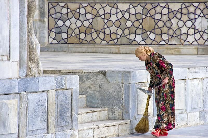 A lady sweeper cleans the marble floor in front of the Ulugbek Medressa.