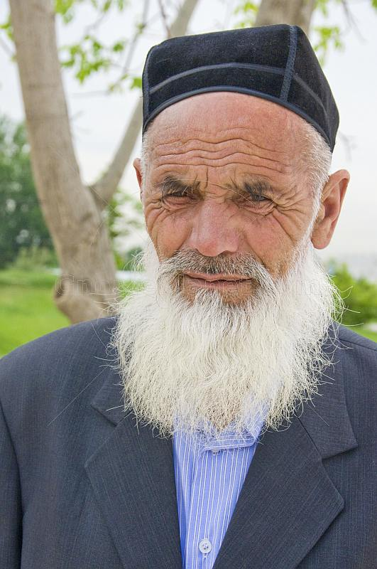 Local elderly Uzbek man with white beard and traditional hat.