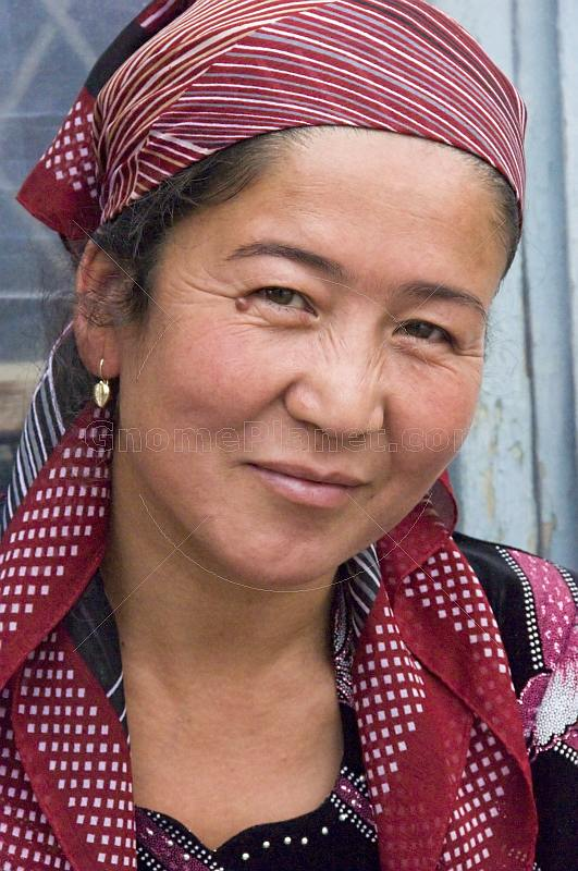 Uzbek lady silk weaver in red headscarf.