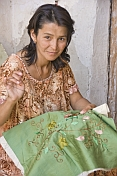 Craftswoman demonstrates her skill with embroidery.
