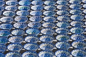 Trader\\\\'s display of blue and white pottery bowls tempts the traveller in Bukhara\\\\'s Central Asian Bazaar.