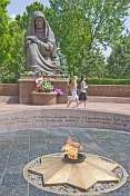 Two girls walk past the Crying Mother war memorial with eternal flame which honours the 400,000 Uzbek soldiers who died in WWII.