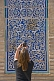 Tourist woman photographs some blue glazed ceramic tilework on the Mohammed Amin Khan Medressa.