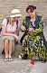 Uzbek craftswoman in Ikat dress shows a tourist some local knitting techniques.