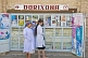 Two nurses stand outside a Pharmacy shop.