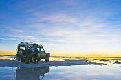 Couple with Land Rover watch the sunset over the Uyuni Salt Flats.