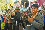 Euphonium players in a brass band marching through the streets in a traditional town festival.