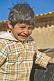 Image of Laughing Bolivian boy in check jacket.