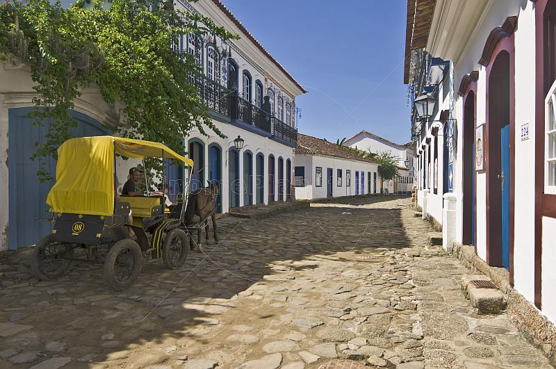 Horse carriage drives along cobbled street in colonial old town.