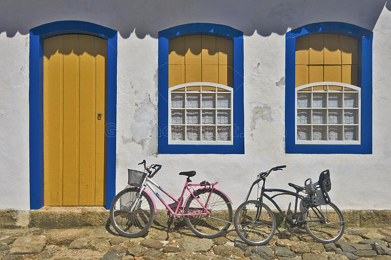 Bicycles in front of colorful colonial house door and windows.