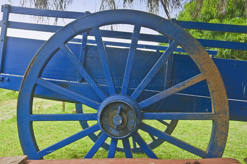 Blue wooden farm cart with mud on the wheel.