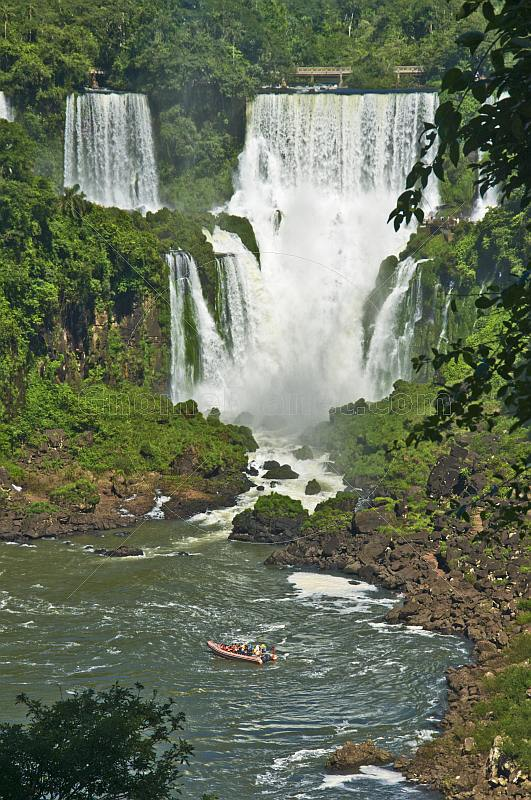 Inflatable boat approaches waterfall at the Iguazu Falls.