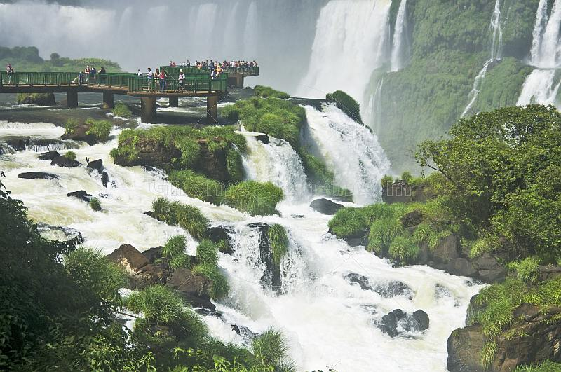 Travellers admire the waterfalls at the Iguazu Falls.