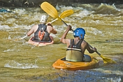 Two canoeists in kayaks negotiate some turbulent water.
