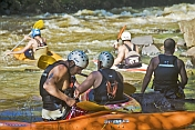 A group of canoeists watch others negotiate rough water.