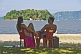 Couple sit on beach looking at island in the Bahia Da Ilha Grande.