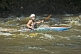 Image of Young canoeist in black kayak negotiates the rapids.