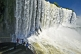 Image of Travellers view the waterfalls cascading into the Iguazu River.