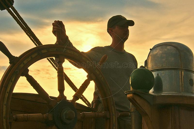 Young trainee seaman takes the wheel of the Barque 'Picton Castle' at sunset.