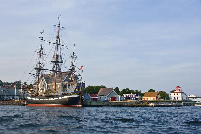 Replica pirate ship \\'Hector\\' moored to the Pictou wharf alongside colonial style buildings.
