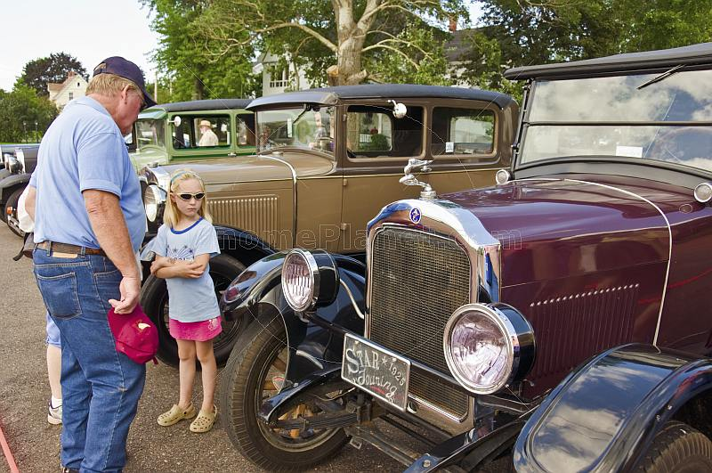 A man and a girl look at a row of vintage motor cars parked on Queens Street.