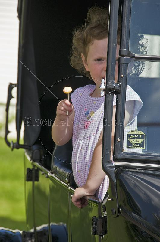 Small girl with lollipop and lilac dress waits in the back of a vintage Model T Ford car.