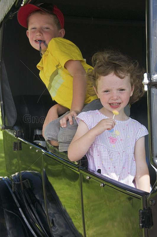 Small girl with lollipop and boy in yellow shirt wait in the back seat of a Model T Ford vintage car.