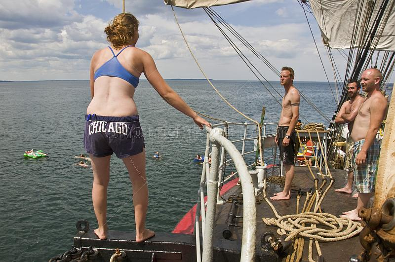Crew of the 'Picton Castle' wait their turn to swing on a rope and swim in the ocean.