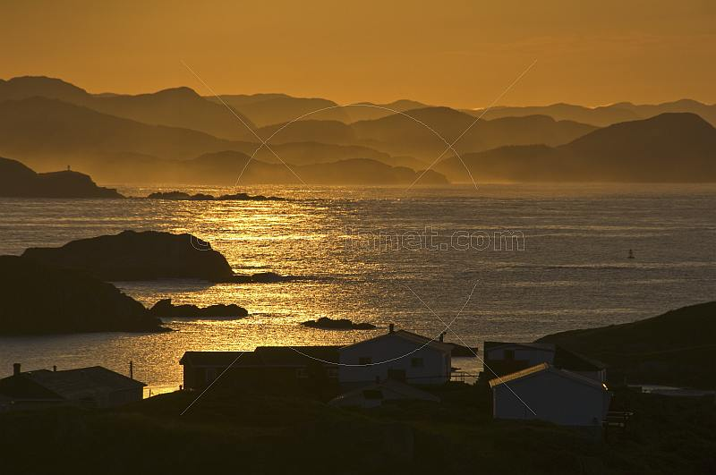 Early morning sun lights the fishing village and distant islands across the ocean inlet.