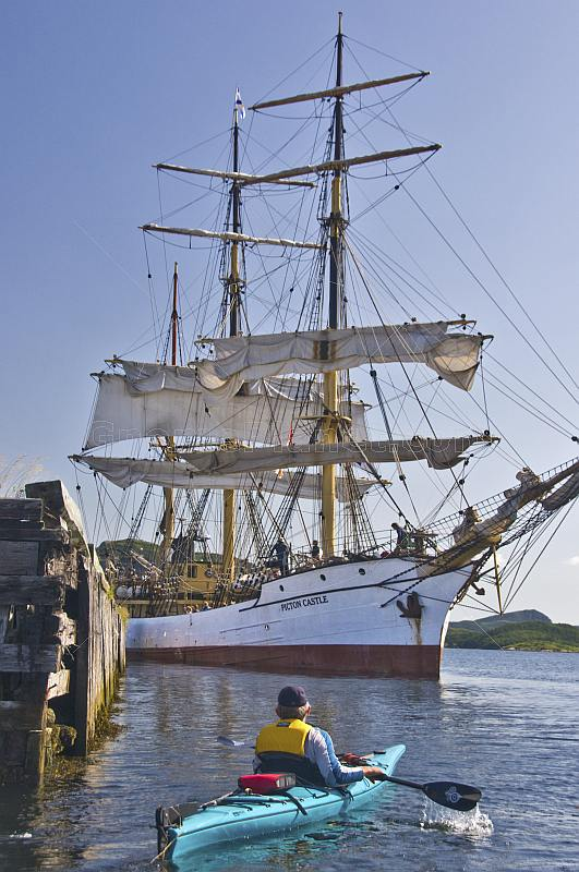 A canoeist watches the tallship 'Picton Castle' prepare to set sail and  leave port.