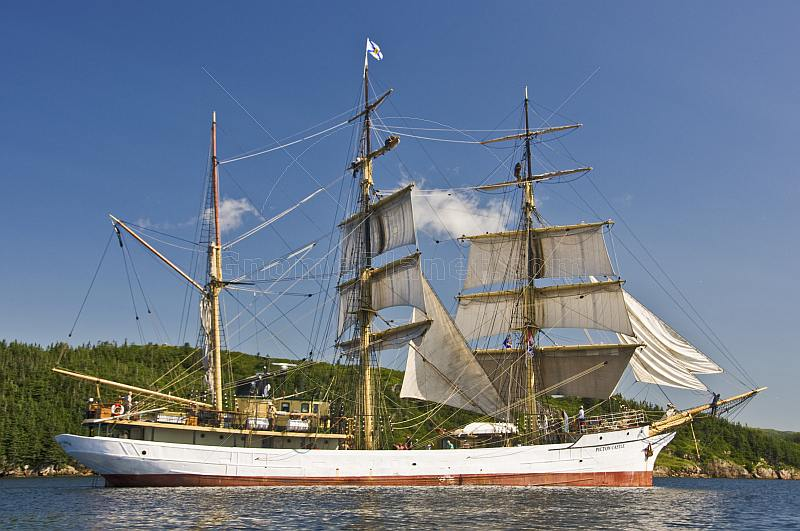 Crew climb the masts and unfurl sail as the barque 'Picton Castle' journeys towards the ocean.