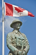 Bronze statue of Canadian soldier stands under National flag on memorial for World War one and two.