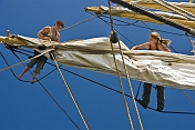 Two women crew members of the tallship 'Picton Castle' work aloft to stow sail.