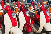 Red and white Honda motor scooters waiting for hire.