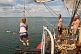 Crew of the \\'Picton Castle\\' wait their turn to swing on a rope and swim in the ocean.