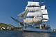The tallship 'Picton Castle' leaves harbor on a sunny morning under full sail.