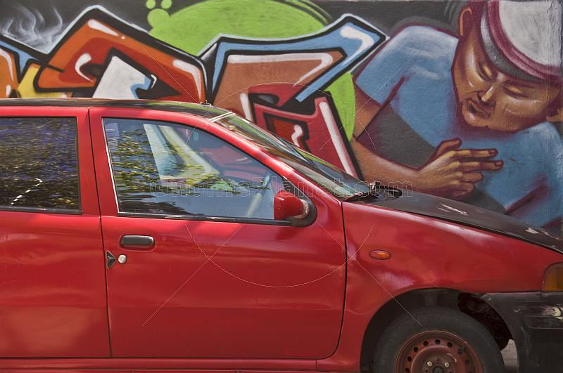 Red car parked in front of wall graffiti.