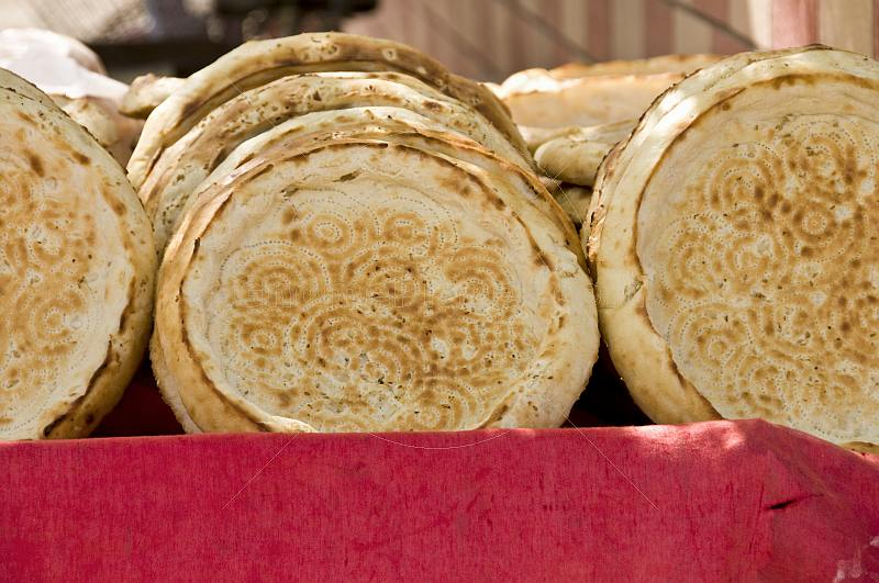 Bread stall with traditional Uighur circular bread loaves that have a flat base, used for eating meat stew.