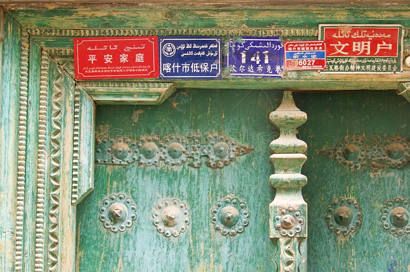 Red and blue signs with Chinese and Uighur writing, on a green door.
