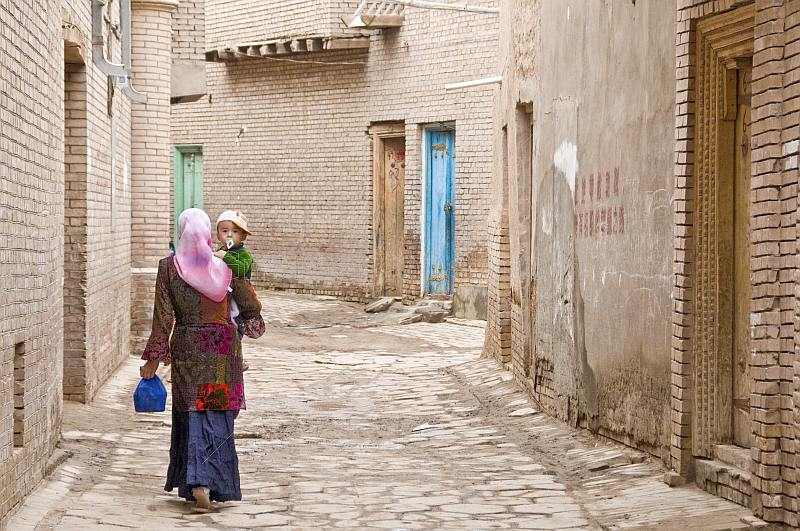 Woman carrying child in the twisting streets of the old city.