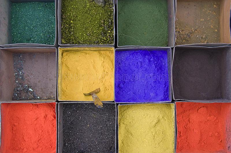 Colored powders in metal display-boxes.