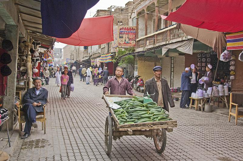 A trader pushes a cart of cucumbers down a busy street in the old city.