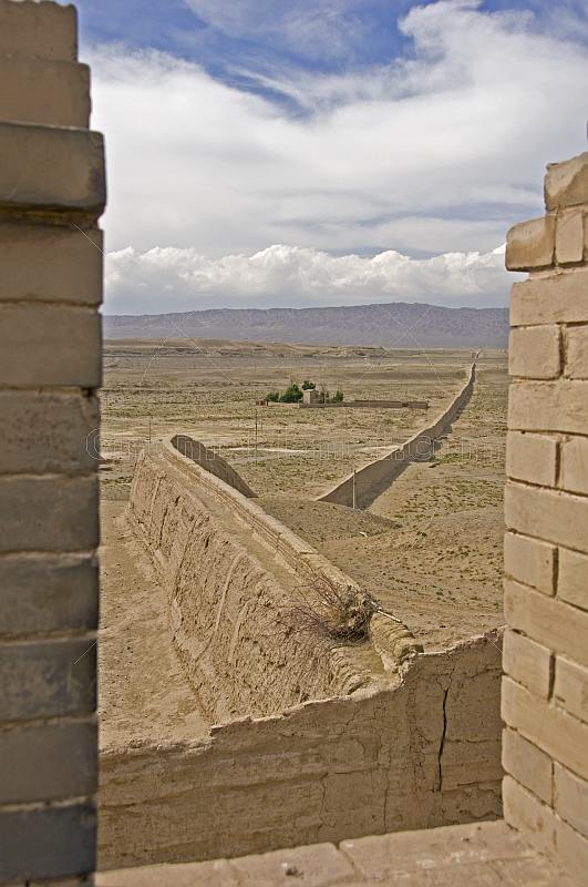 The Great Wall of China snakes away across the desert from the Jiayuguan Fort.
