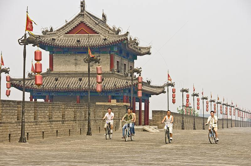 Chinese men ride bicycles along the city walls.