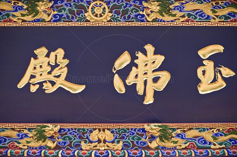 Gold Chinese characters on a black background with painted border, at the Dazhao Lamasery.