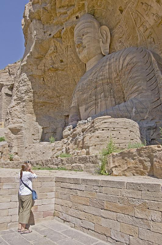 Western woman photographing a giant Buddha statue at the Yungang Buddhist caves, near Datong.