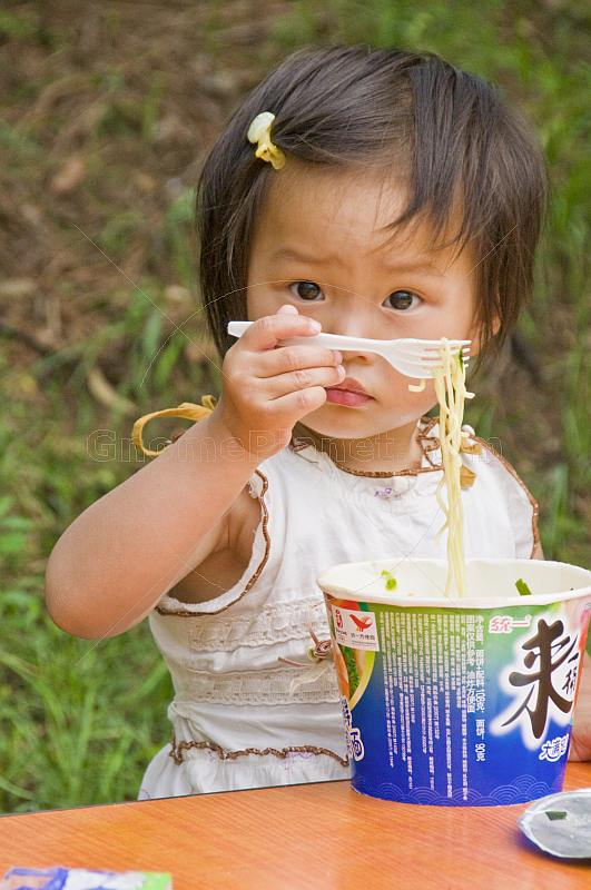 Young girl eating noodles at the Lily Lake of the Bishu Shanzhuang summer resort for Qing Emperors.